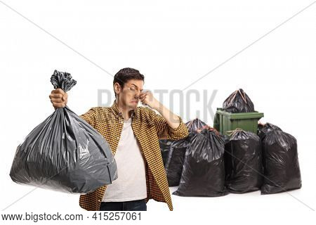 Young man holding a smelly bin bag in front of a waste bin isolated on white background