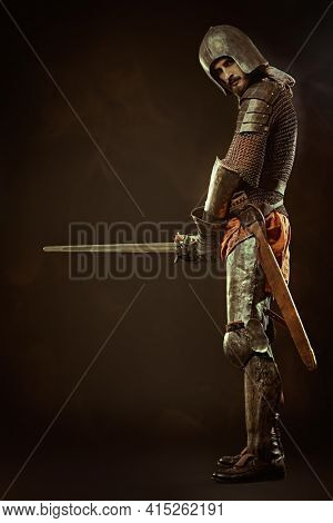 Full length portrait of a courageous medieval knight with a sword on a black background.