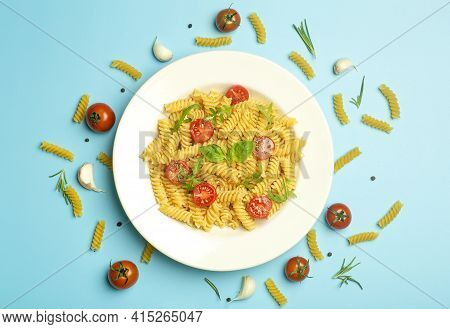 Food Pasta On A Blue Background. Italian Fusilli Pasta With Tomatoes, Herbs And Basil On A White Pla