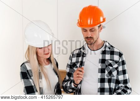 Two Designers In Helmets And Plaid Shirts Discuss A List Of Additions On Site. The Concept Of Buildi
