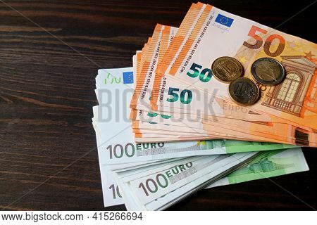 Bundle Of Euro Banknotes And Coins On Dark Brown Wooden Background With Copy Space