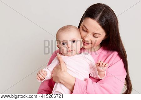 Shot Of Loving Mother Holding And Hugging Baby In Her Hands, Woman With Dark Hair Wearing Casual Pin