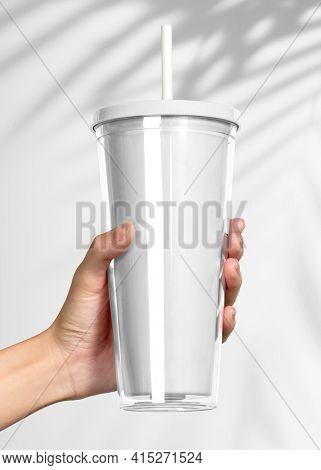 Hand holding blank white tumbler