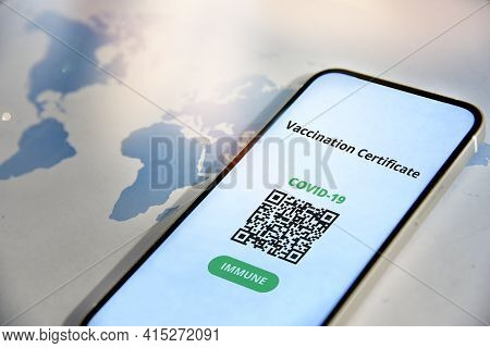 Mobile Phone  With Digital Certificate Of Vaccination Against Covid-19 In Front Of The World Map. Tr