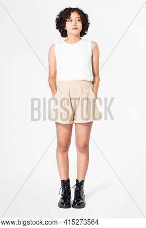 Woman in white tank top and beige shorts with design space summer apparel