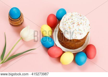Easter Cake On A Plate With Colorful Easter Eggs And A Tulip Flower On The Pink Background. Traditio