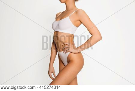 Close-up Slim Tanned Female Body In Underwear Over White Background.
