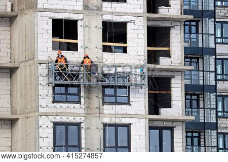 Workers Standing On Lifting Platform Near The Wall Of Unfinished House. Construction Works, Resident