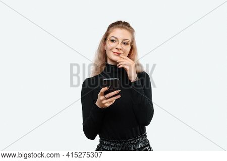 Image Of A Thoughtful Young Beautiful Woman In Casual Clothes Holding Her Smart Phone. Technology, Y