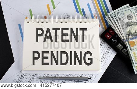 Patent Pending Text Written On Notebook With Chart,calculator And Dollars