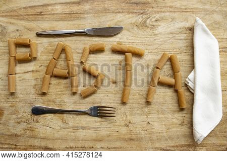 Written Pasta Made With Wholemeal Rigatoni On Woodentable