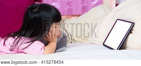 Girl Lying Watching Cartoon From Tablet On Soft White Mattress. 4 Year Old Child With Support Chin.
