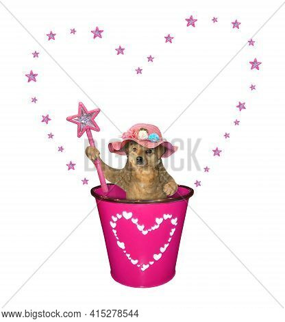 A Beige Dog In A Straw Hat With A Magic Wand  Is In A Pink Pail. White Background. Isolated.