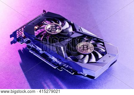 Two Gold Bitcoin On A  Video Card With Purple Backlight In The Style Of Cyberpunk. Crypto Currency.