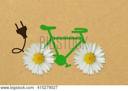 Green Paper Bicycle With Daisy Flowers And Electric Plug On Recycled Paper Background - Concept Of E