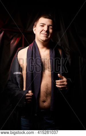 A Plump Man With A Bare Tummy And A Black Scarf On A Black Background