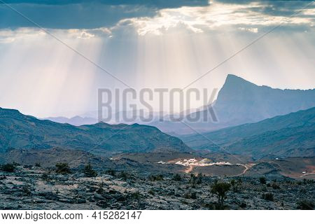 Rays Of Sunlight Shine Through Scattered Clouds On A Small Arabian Village In Jebel Shams Mountains,