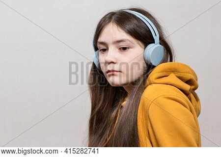 A Sad Teenage Girl, 12-13 Years Old, Sits In Headphones Sweatshirt On A White Background Copy Space