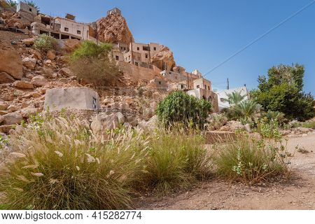 An Old Arabian Village In The Gorge Of Wadi Tiwi In Oman On A Hot Day. Houses Sticked To The Steep C