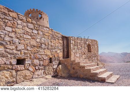 Stone Wall Of A Small Medieval Arabian Fort With Wooden Door And Stone Stairs In Bukha, Oman. Hazy D