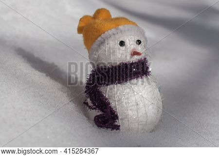 Toy Snowman In The Snow Under The Sun's Rays