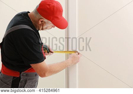 Worker In Red Cap And Work Suit With The Measuring Tape. Man Is Installing The Doors. Measure Tape I