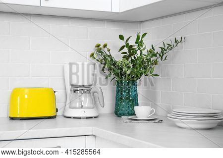 Modern Yellow Toaster, Coffeemaker And Dishware On Countertop In Kitchen