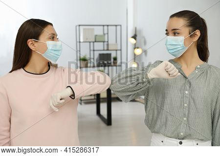 Women Greeting Each Other By Bumping Elbows Instead Of Handshake In Office
