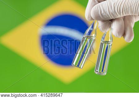Doctor Holding Coronavirus Vaccine In His Hand. Coronavirus Vaccine With The Flag Of Brazil In The B