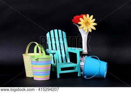Colorful Sand Pails, Miniature Adirondack Chair And Silk Flowers In Vase Shot In Studio Showing Spri
