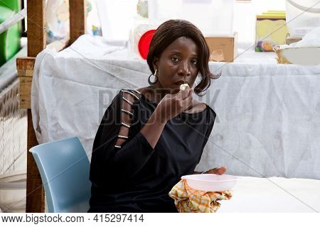 Young Saleswoman Sitting Behind Her Sales Stands And Eating A Boiled Egg