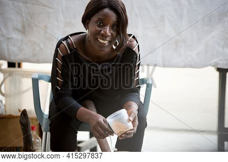 Smiling Saleswoman Sitting At The Market Behind Her Display And Pounding The Dried Spices