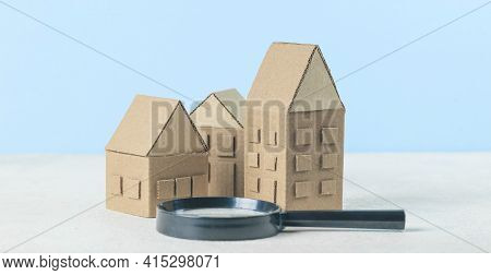 Finding Or Choosing The Best Home. Magnifying Glass And Cardboard Miniature Houses. Sale Or Rental O