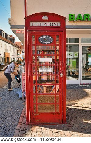 Hofheim, Germany - March 2020: Public Bookcase In Old Red Telephone Box. A Cabinet Which May Be Free