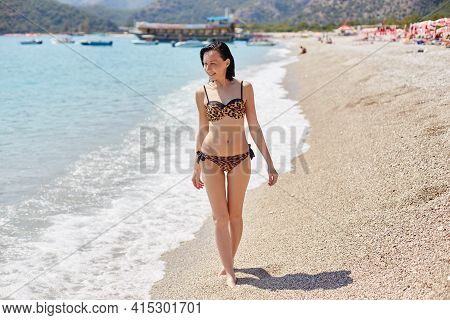 Beautiful Slender Woman In A Swimsuit Is Relaxing On The Beach In Turkey. Tourist Holidays In Fethiy