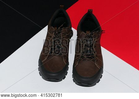 Stylish Mens Sneakers Or Leather Brown Shoes On A Colored Background.