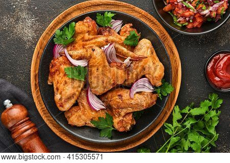 Grilled Chicken Wings Or Roasted Bbq With Spices And Tomato Salsa Sauce On A Black Plate. Top View W