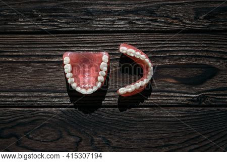 Full Removable Plastic Denture Of The Jaws. A Set Of Dentures On A Dark Background. Two Acrylic Dent