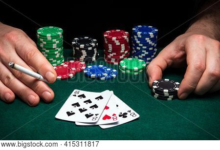 Hands Of Gambler Closeup And Chips On Green Table In A Poker Club. A Player Places A Bet On Winning