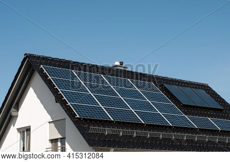 A Residential Building With Solar Panels On The Roof For Sustainable Energy