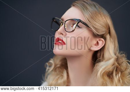 Close-up portrait of a fashionable blonde woman lookin up in elegant glasses. Optics, eyewear. Business style.