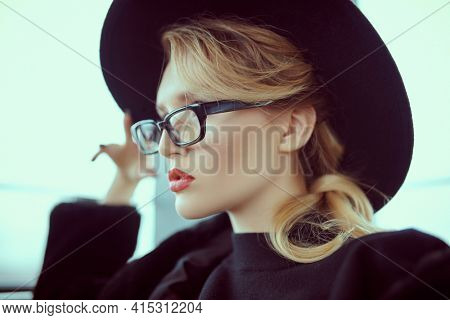 Close-up portrait of a fashionable young woman in modern glasses and hat in interiors. Beauty, fashion concept. Optics, eyewear.