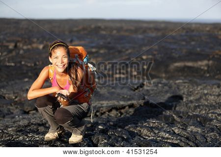 Hiker showing fresh cooled lava from Kilauea volcano around Hawaii volcanoes national park, Big Island, Hawaii, USA. Young asian woman hiking.