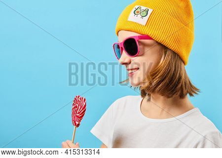 Hipster Teen Girl In Trendy Glasses Wearing Knitted Hat And Holding Lollipop. Pretty Fashionable Wom