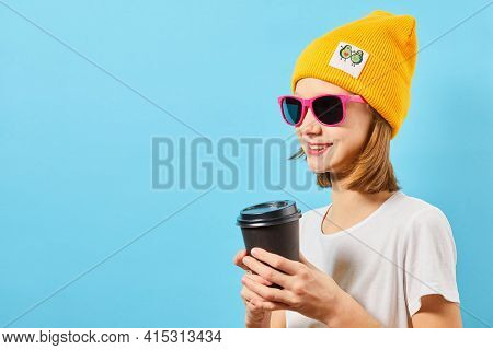 Young Caucasian Girl With Blonde Hair, In Glasses Wearing Shirt With Knitted Hat On A Pink Backgroun