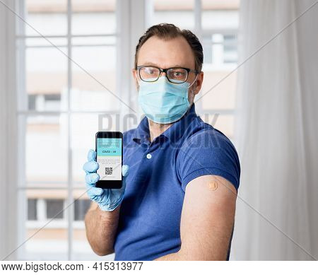 Covid-19 Vaccination Record. Man Holding Cellphone With Covid-19 Vaccination Record. Covid-19 Vaccin