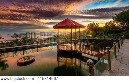 Pavilion on the pond at sunset. nha Trang city on background. Vietnam. Panorama