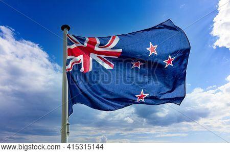 New Zealand Flag Waving Against Blue Cloudy Sky