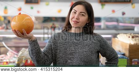 Young Caucasian Woman In A Supermarket Buys Vegetables. Holds A Pomelo In His Hands. Citrus Buying C