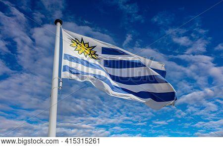Uruguay Flag, Oriental Republic Of Uruguay National Symbol On A Flagpole Waving Against Blue Cloudy